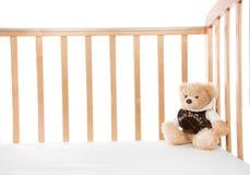 Cama de bebé con el oso de peluche para el niño foto de archivo