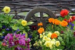 Cama de flor decorativa con una rueda de madera landscaping imagenes de archivo