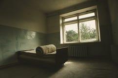 Cama de hospital en un cuarto abandonado en ruinas con la luz que viene a través de las ventanas Imagen de archivo libre de regalías