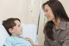 Cama de hospital paciente del niño joven del muchacho con la madre Foto de archivo