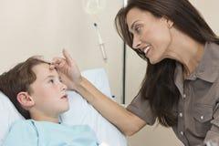 Cama de hospital paciente del niño joven del muchacho con la madre Fotografía de archivo
