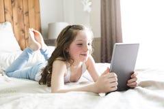Cama de la endecha de la muchacha en casa con tecnología de la tableta Imágenes de archivo libres de regalías