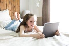 Cama de la endecha de la muchacha en casa con tecnología de la tableta Imagen de archivo libre de regalías