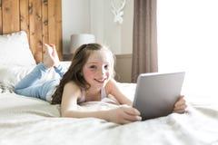 Cama de la endecha de la muchacha en casa con tecnología de la tableta Fotos de archivo libres de regalías