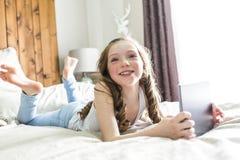 Cama de la endecha de la muchacha en casa con tecnología de la tableta Imagenes de archivo