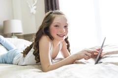 Cama de la endecha de la muchacha en casa con tecnología de la tableta Foto de archivo libre de regalías