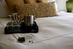 Cama de lujo de la habitación con las bebidas bandeja e iPod Imagen de archivo libre de regalías