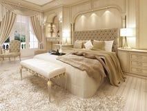 Cama de lujo en un dormitorio neoclásico grande con el lugar decorativo Foto de archivo libre de regalías