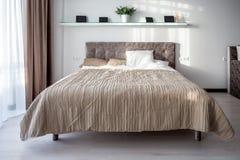 Cama de madera en el interior del dormitorio moderno en plano del desv?n en apartamentos costosos fotos de archivo