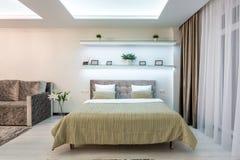 Cama de madera en el interior del dormitorio moderno en plano del desv?n en apartamentos costosos imágenes de archivo libres de regalías