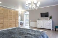 Cama de madera en el interior del dormitorio moderno en plano del desv?n en apartamentos costosos fotografía de archivo libre de regalías
