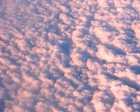 A cama de nuvens brancas róseos no céu capturou do ar Fotos de Stock Royalty Free