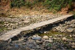 Cama de río pedregosa seca con el puente de bambú Imágenes de archivo libres de regalías