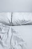 Cama desarrumado com bedclothes cinzentos fotografia de stock royalty free