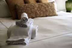 Cama do quarto do hotel de luxo com toalhas Fotos de Stock