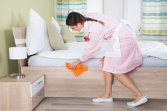 Cama femenina de la limpieza del ama de casa fotografía de archivo libre de regalías