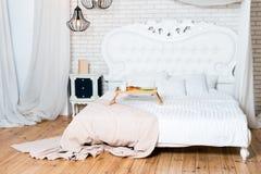Cama gigante en el apartamento del desván Desayuno en cama, una bandeja de café, cruasanes y flores honeymoon Madrugada en foto de archivo