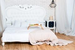 Cama gigante en el apartamento del desván Desayuno en cama, una bandeja de café, cruasanes y flores honeymoon Madrugada en imagen de archivo