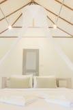 Cama gigante y dormitorios netos de las cortinas imagen de archivo