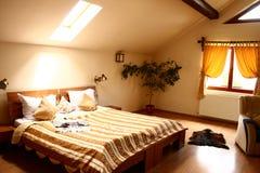 Cama grande em um quarto de hotel no sótão Imagem de Stock Royalty Free