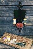 Cama, hilo y tijeras de aguja en el fondo de madera Fotos de archivo