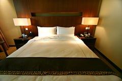 Cama matrimonial del dormitorio del hotel Imágenes de archivo libres de regalías