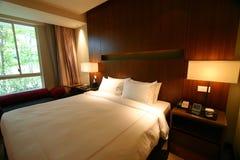 Cama matrimonial del dormitorio del hotel Foto de archivo