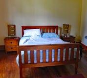 Cama matrimonial enmarcada de madera en una propiedad de alquiler peculiar en Masterton en Nueva Zelanda imagen de archivo