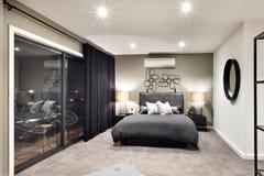 Cama negra del color en hotel lujoso con las lámparas que destellan Fotografía de archivo