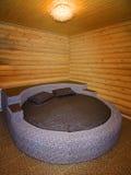 Cama redonda en un dormitorio de madera Foto de archivo libre de regalías