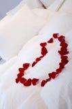 Cama romántica con el corazón de rosas Fotos de archivo