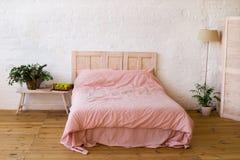 Cama vacía con las almohadas rosadas y la cubierta rosada en el dormitorio Imágenes de archivo libres de regalías