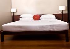 Cama y cabecero en dormitorio con la lámpara. Imagen de archivo