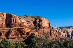 Camadas em montanhas vermelhas da rocha contra o fundo do céu azul Fotografia de Stock