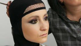 Camaleão multi-colorido elegante da sombra para os olhos com cor de prata cinzenta roxa amarela na pálpebra da menina bonita vídeos de arquivo