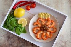 Camarón frito en un disco, albahaca fragante, limones, pimientos picantes, tomates en una bandeja hermosa imagenes de archivo