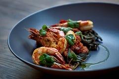 Camarões cozinhados, camarões com temperos no fundo de pedra Camarão fritado com alecrins em uma frigideira repartida em uma tabe Imagens de Stock