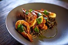 Camarões cozinhados, camarões com temperos no fundo de pedra Camarão fritado com alecrins em uma frigideira repartida em uma tabe Imagem de Stock