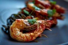 Camarões cozinhados, camarões com temperos no fundo de pedra Camarão fritado com alecrins em uma frigideira repartida em uma tabe Fotos de Stock
