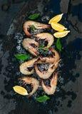 Camarões crus frescos com limão, ervas e especiarias no gelo lascado sobre o contexto escuro da pedra da ardósia foto de stock