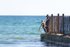 Camarões da pesca do menino no mar do cais velho Fotografia de Stock Royalty Free