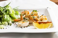 Camarões do tigre em espetos com limão e verdes no prato branco Imagens de Stock