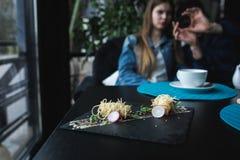 Camarões do tigre em macarronetes chineses com molho na placa preta Conceito asiático do alimento Povos no fundo no lugar do rest Fotografia de Stock Royalty Free