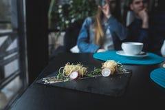 Camarões do tigre em macarronetes chineses com molho na placa preta Conceito asiático do alimento Povos no fundo no lugar do rest Fotografia de Stock