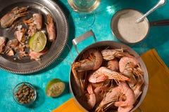 Camarões e molho saboroso na opinião superior do fundo ciano imagens de stock royalty free
