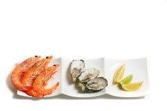Camarões e ostras em uma placa isolada no branco Fotografia de Stock Royalty Free