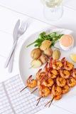 Camarões grelhados com as batatas na placa branca Fotos de Stock