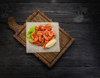Camarões grelhados em uma placa sobre o fundo de madeira escuro Foto de Stock Royalty Free