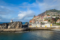 Camara de Lobos old town harbor. Camara de Lobos fishing village on the hills and harbor with volcanic rocks. Popular touristic resort at Madeira island Stock Photography