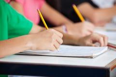 Camarades de classe écrivant dans le livre au bureau Photographie stock libre de droits